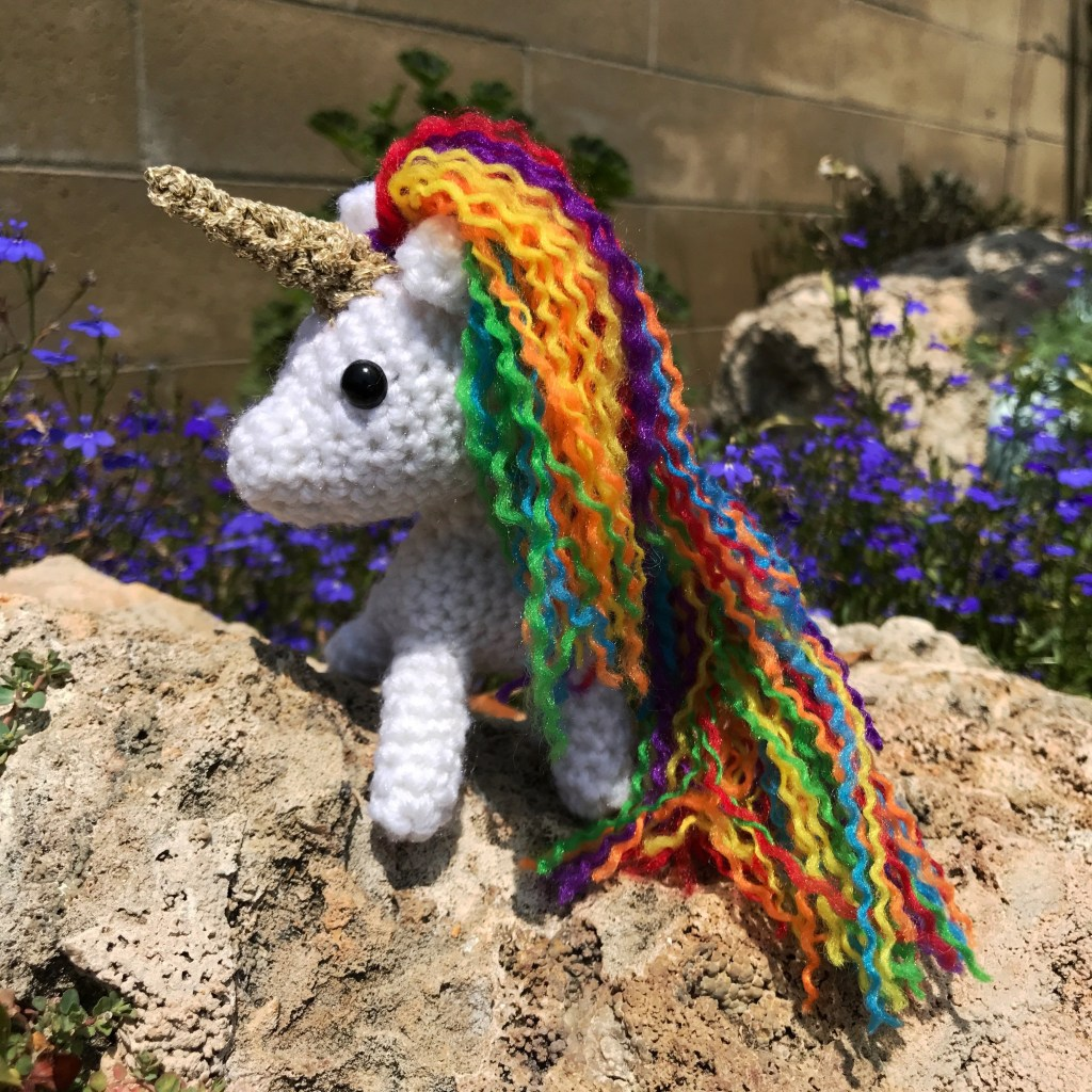 small crocheted unicorn with rainbow mane and tail