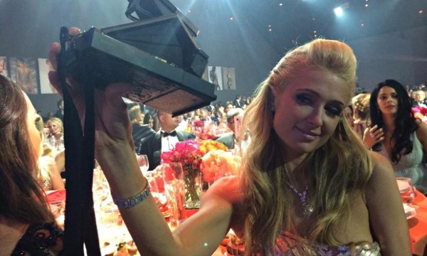 Paris Hilton taking a Polaroid photo