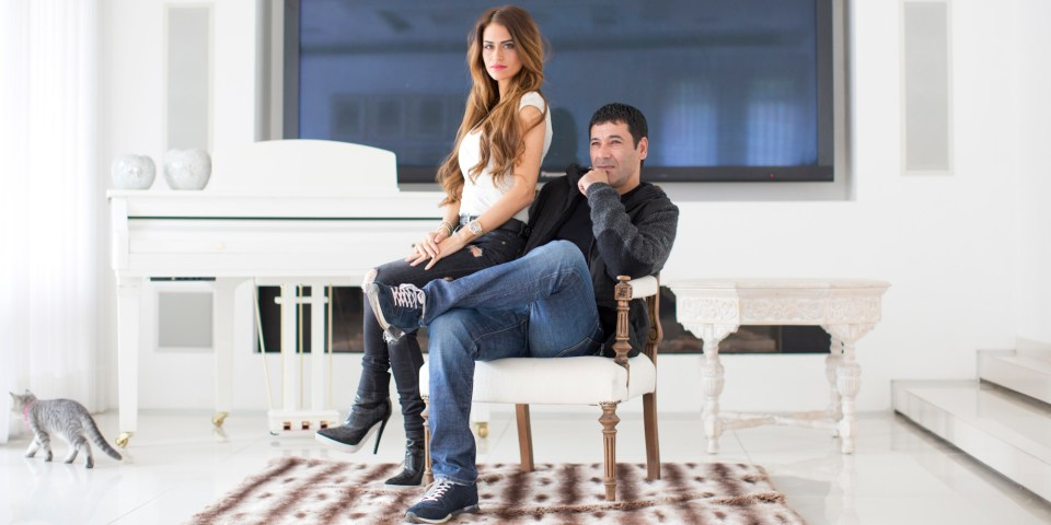 Gilbert Chikli, 50, and his wife Shirly Chikli, 31, pose for a photo at their home in Ashdod, Israel, Monday, March 28, 2016. Chikli, a visionary fraudster, ripped off some of the world's biggest corporations, and then laundered millions in China, which is serving as a massive money laundering machine for foreign criminals, an AP investigation has found. (AP Photo/Oded Balilty)