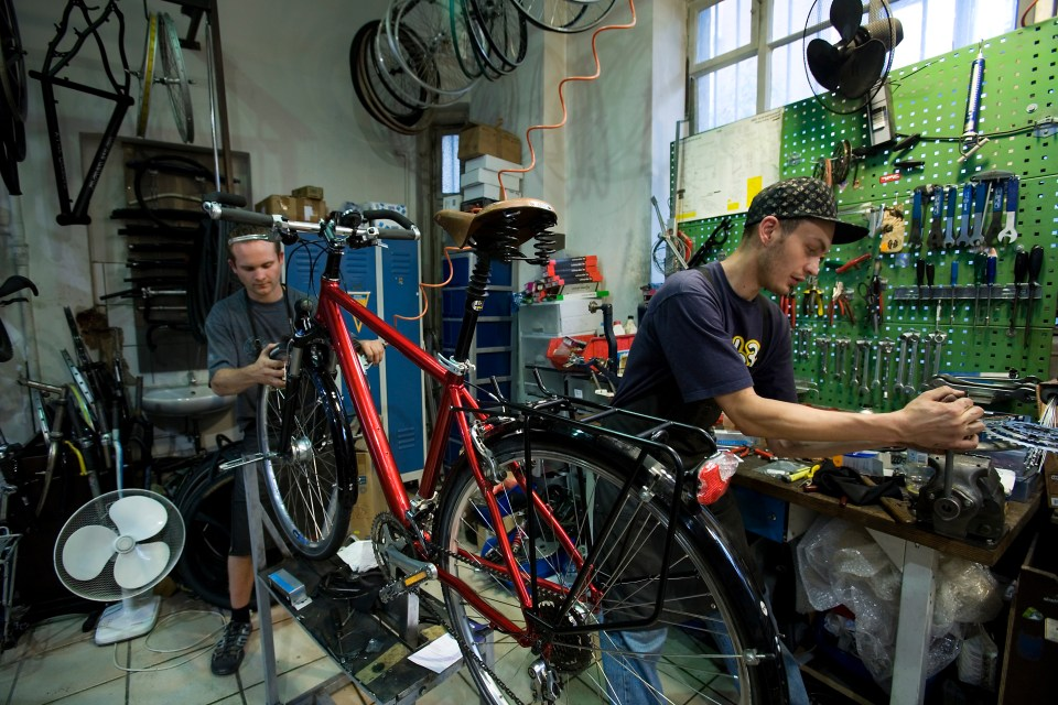 repairs bicycle tools wrenches fan fans red bike cycle cyclists man men work working mechanic mechanics tinker fix saddle handlebars seat wheel wheels spokes crossbar chain sprocket sprockets tools cycles mechanic workshop vehicle vehicles bicycles work