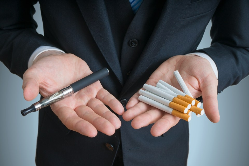 Man Is Holding Vaporizer And Conventional Tobacco Cigarettes And