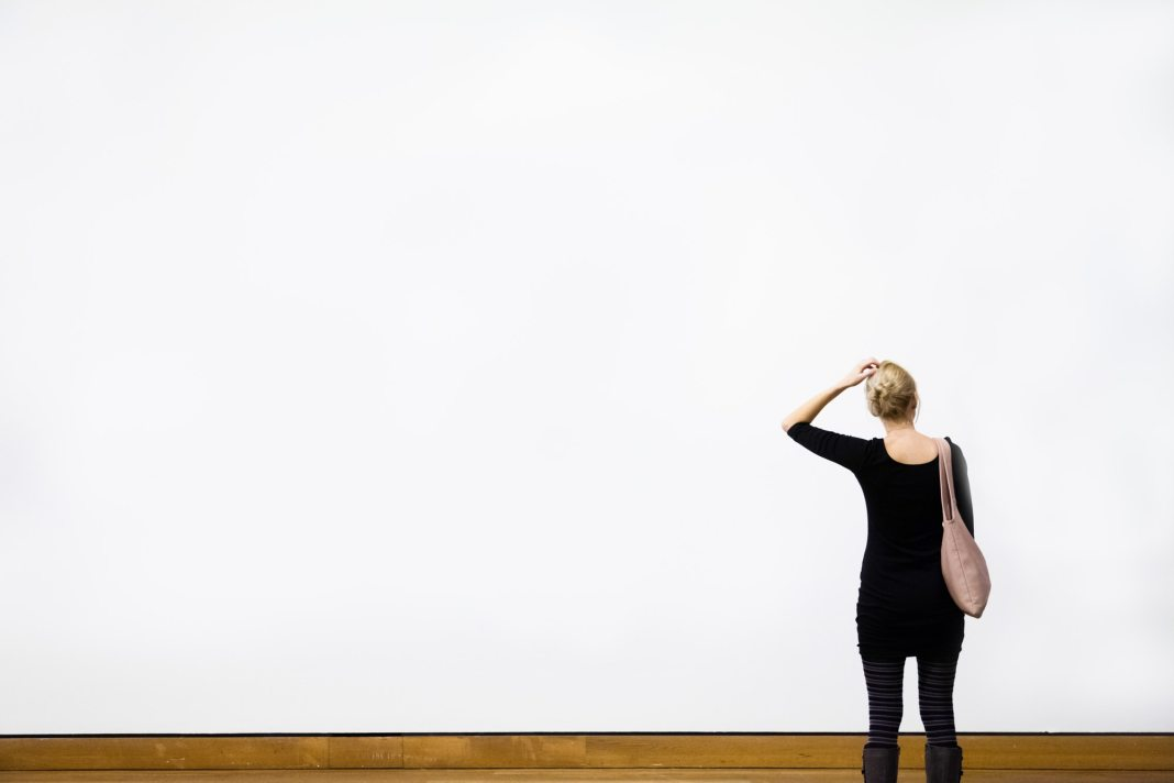 Woman Questioning in front of a Blank Wall