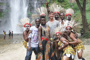 Junior music performance major Jeremy Feight poses with a group of Ghanaian musicians and dancers during the filming of a television commercial in Ghana.