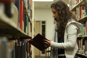 Photo by Claire Murray | The Duquesne Duke. Freshman early childhood education major Elizabeth Osche picks out a book in the Gumberg Library. Students who want to read for pleasure can visit the McNaughten Popular Book Collection across from the front desk at the library.