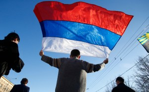 AP Photo. An activist carries a Russian flag during a rally at a central square in eastern Ukraine on March 23.