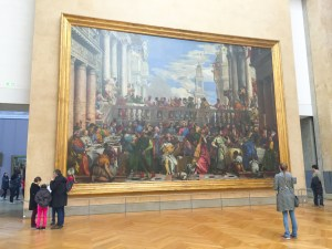 "Photo by Rebekah Devorak | Opinions Editor. ""The Wedding at Cana,"" by Paolo Veronese, hangs directly across from the ""Mona Lisa"" in the Louvre."