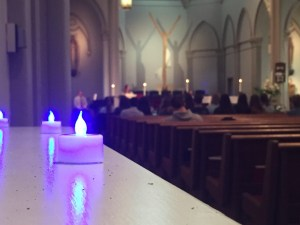 Kaye Burnet/ News Editor Blue candles illuminate the campus chapel Wednesday during a mass for childhood grief awareness. On April 20, a Duquesne social justice class will host child grief awareness events, including dyeing the campus fountains blue.