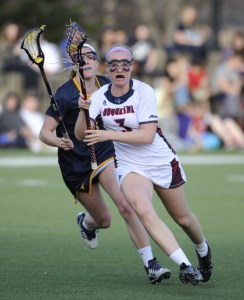 Courtesy of the Athletic Department - Senior midfielder Meredith Micho carries the ball past a defender during a 2015 matchup with the West Virginia Mountaineers. The Dukes split their first two conference matchups this past weekend.