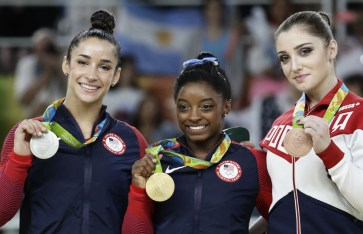 Bronze medallist Russia's Aliya Mustafina, right, gold medallist United States' Simone Biles, center, and silver medallist United States' Aly Raisman display their medals for the artistic gymnastics women's individual all-around final at the 2016 Summer Olympics in Rio de Janeiro, Brazil, Thursday, Aug. 11, 2016. (AP Photo/Dmitri Lovetsky)