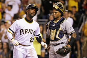 Pittsburgh Pirates' Andrew McCutchen, left, crosses home plate in front of Milwaukee Brewers catcher Martin Maldonado after hitting a solo home run off Milwaukee Brewers relief pitcher Carlos Torres in the seventh inning of a baseball game in Pittsburgh, Saturday, Sept. 3, 2016. (AP Photo/Gene J. Puskar)