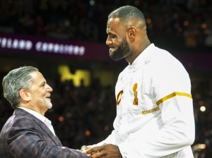Cleveland Cavaliers' LeBron James accepts his NBA championship ring from Cavaliers owner Dan Gilbert before a basketball game against the New York Knicks in Cleveland, Tuesday, Oct. 25, 2016. (AP Photo/Phil Long)