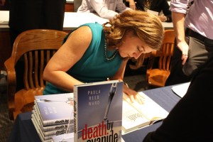 Kailey Love | Photo Editor  Paula Reed Ward signs a book at an event in the law school on Oct. 4. Ward has taught investigative reporting classes at Pittsburgh universities including Duquesne.