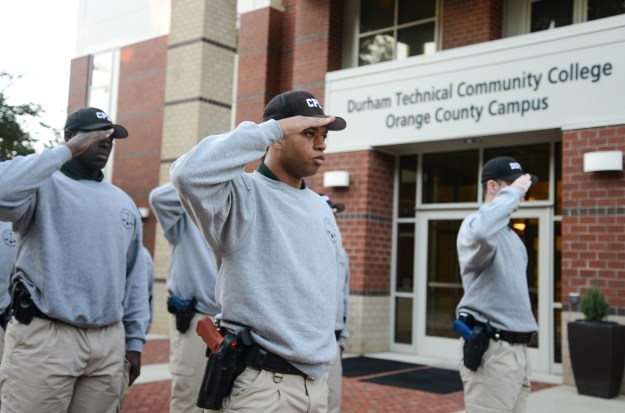 Cadets stand in front of Durham Tech Orange County campus and salute flag