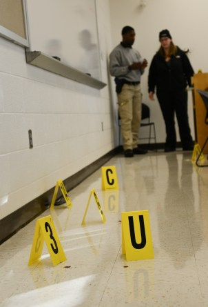 Two students look at yellow evidence markers in mock crime scene