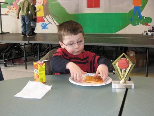 Colin eating pizza at the banquet