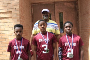 Coach Walter Dunn, pictured with three captains from the DOT Trojans