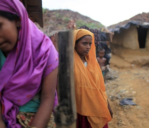 Rohingya women stand in front of their makeshift home in an unregistered Rohingya refugee camp in Teknaf