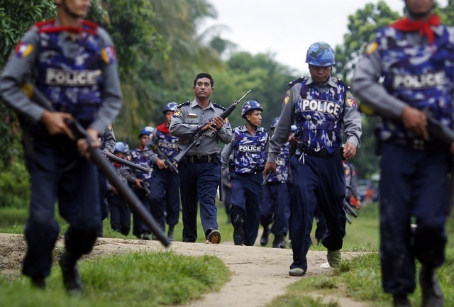 Policemen carry their weapons during fighting between Arakanese and Rohingya communities in Sittwe, Arakan state. (Reuters)