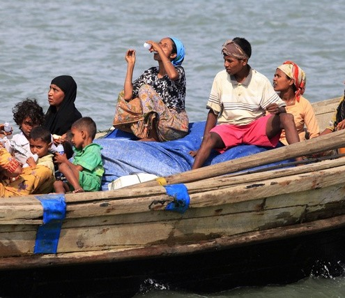 Myanmar's Muslim Rohingya people on a boat cross the river Naf, from Myanmar into Bangladesh, in Teknaf