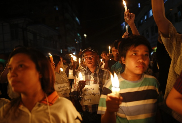 Demonstrators hold candles in a protest against the government's decision to raise electricity prices in Rangoon (Reuters)