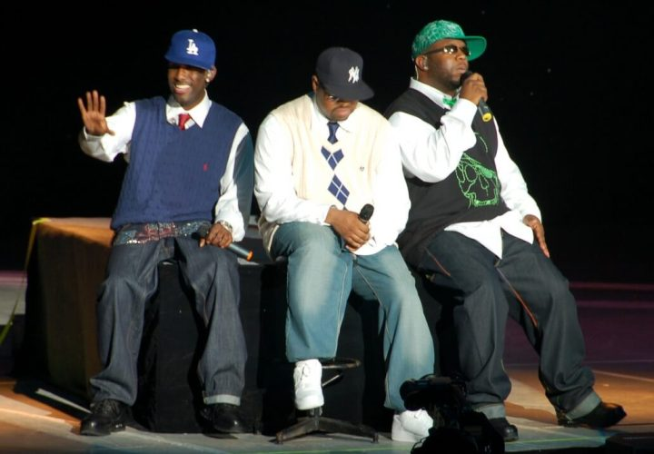 Boyz II Men on stage, sitting, and singing