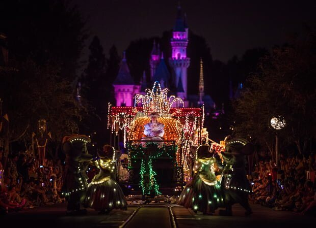 Disneyland electrical parade with castle and pumpkin carriage lit at night