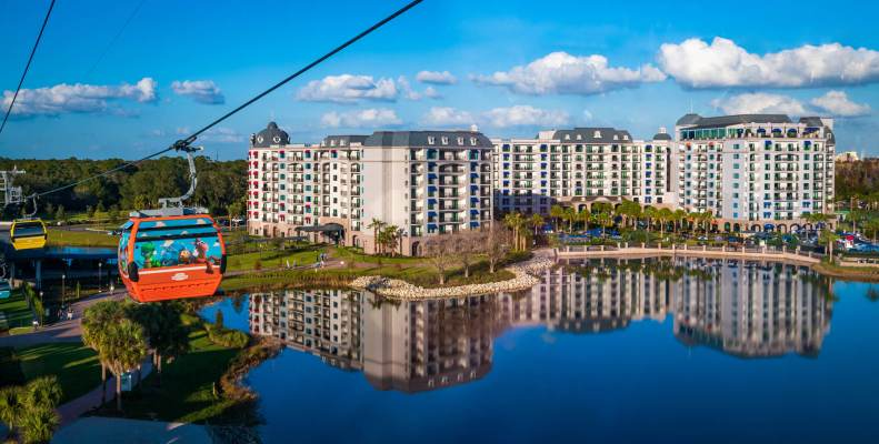 Riviera dvc resort hotel at Disney World, surrounded by palm trees and clear blue skies