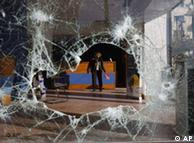 A woman, seen through a shattered storefront, clears debris inside a riot-damaged travel agency in central Athens