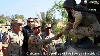 Egyptian President, Abdel Fattah al-Sisi (C), shaking hands with a member of the armed forces during his official visit following unprecedented attacks in North Sinai, Egypt, 04 July 2014 (Photo: EPA/OFFICE OF THE EGYPTIAN PRESIDENT / HANDOUT HANDOUT EDITORIAL USE ONLY/NO SALES +++(c) dpa - Bildfunk+++)