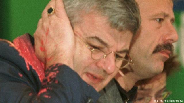 Von einem Farbbeutel getroffen faßt sich Bundesaußenminister Joschka Fischer erschrocken an sein rechtes Ohr. Der Farbbeutel wurde am Donnerstag (13.05.1999) während des Bündnis 90 / Die Grünen-Sonderparteitages über den Kosovo-Krieg in Bielefeld von einem Mann auf Fischer geworfen. (Bild: dpa)