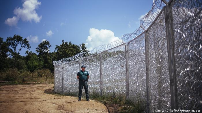 A guard stands watch in front off a barbed wire fence (Dimitar Dilkoff/AFP/Getty Images)