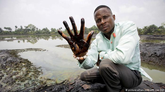 A man is showing his hand covered with oil (picture-alliance/dpa/M. van Dijl)