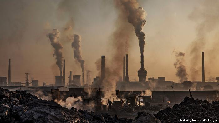 Smoke billows from a large steel plant as a Chinese labourer works at an unauthorized steel factory (Getty Images/K. Frayer)