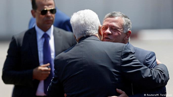 Jordan's King Abdullah II is hugged by Palestinian President Mahmoud Abbas
