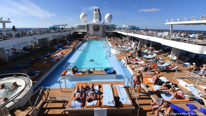 Menschen am Pool auf einem Kreuzfahrtschiff (picture-alliance/dpa/A.Warnecke)