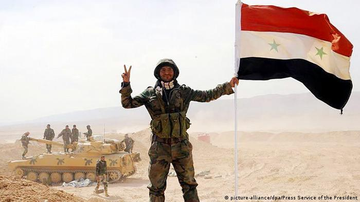Syrian soldier brandishes the Syrian flag in Deir el-Zour, witha tank and fellow soldiers in the background