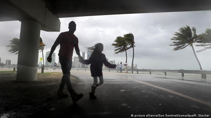 Man and daughter run under bridge in Miami