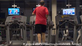 A man watches the TV debate between Merkel and Schulz at a fitness center