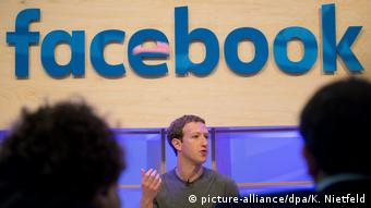 Facebook CEO Mark Zuckerberg gestures during a speech with the Facebook logo in the background (picture-alliance/dpa/K. Nietfeld)