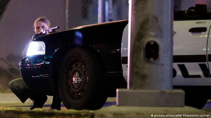 A police officer takes cover behind a vehicle (picture-alliance/AP Photo/John Locher)