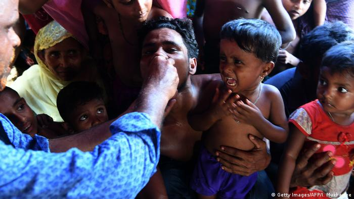 A Rohingya refugee child reacts as a Bangladeshi volunteer administers an oral cholera vaccine to her father