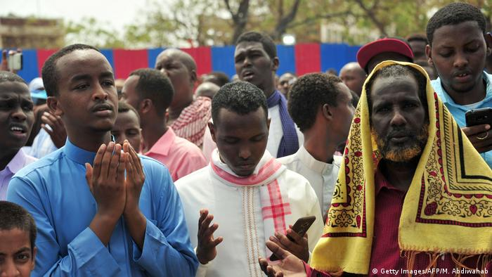 Somali men pray during a memorial for the slain victims of a massive truck bomb.