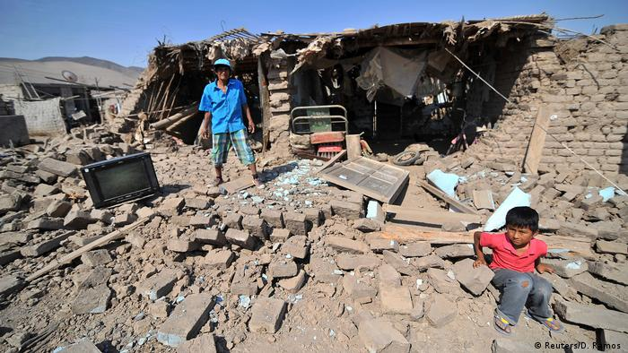A man and a child in the rubble in Peru (Reuters/D. Ramos)