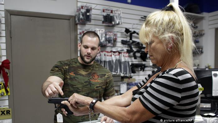 A man showing a woman how to use a gun in a store in Florida (picture-alliance/AP Photo/L. Sladky)