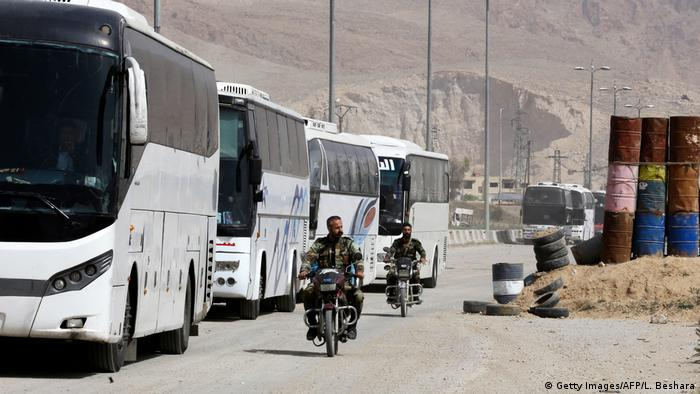 Motorbikes passing by buses awaiting evacuees (Getty Images/AFP/L. Beshara)