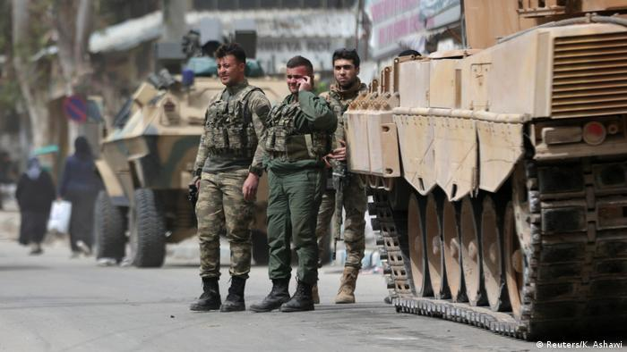 Turkish soldiers are seen standing next to a tank in the center of Afrin, Syria.