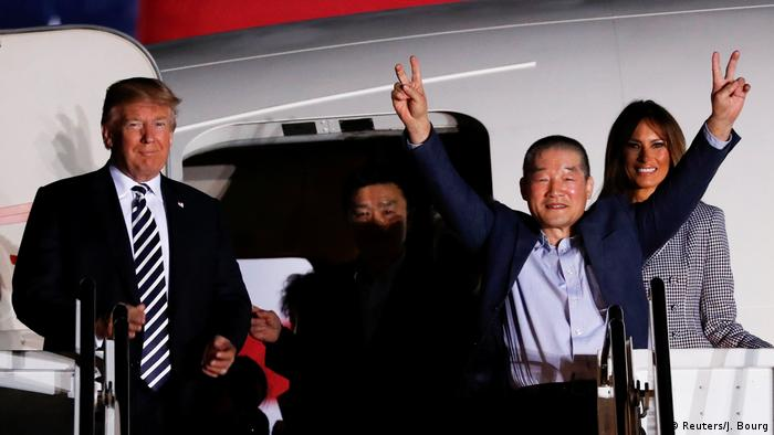 Trump smiles as a freed prisoner flashes a victory sign while stepping off a plane (Reuters/J. Bourg)