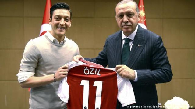 Özil pictured handing a football jersey to Erdogan (picture-alliance / dpa / Uncredited / Presdential Press Service)