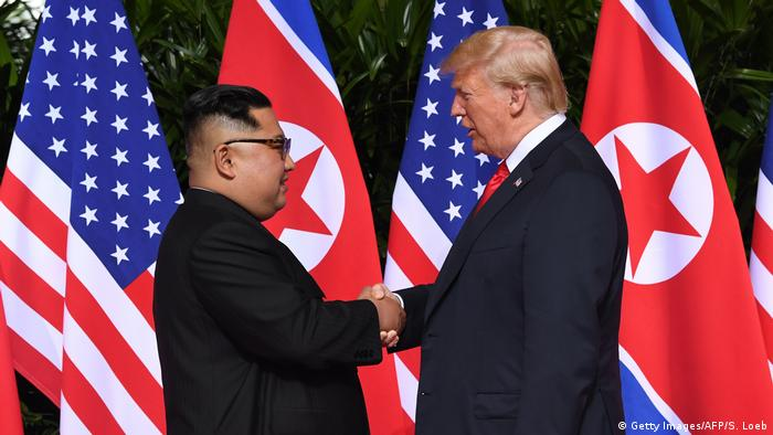 North Korea's leader Kim Jong Un (L) shakes hands with US President Donald Trump