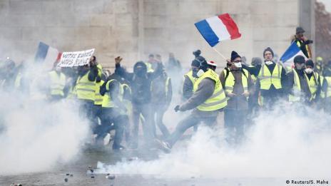 Manifestantes com coletes amarelos segurando bandeiras francesas em meio a uma nuvem de gás lacrimogêneo